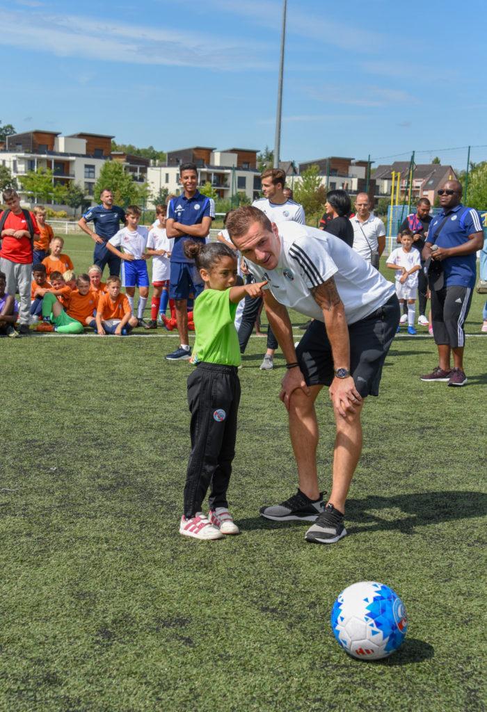 ete foot 2019, un enfant avec un joueur de foot du racing club de Strasbourg